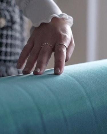 Hand streicht über blaues Samtsofa